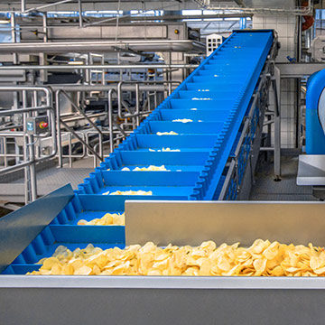Incline conveying of potato chips and snack foods