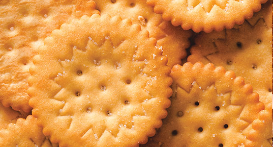 Oil spray and salt application on crackers and other foods